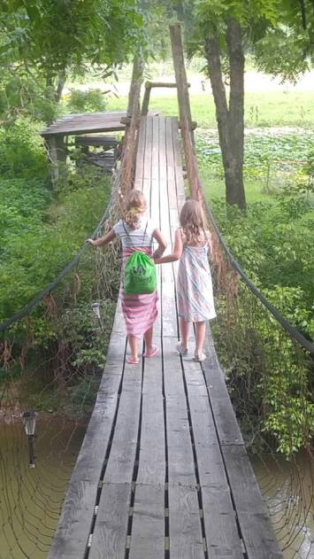 girls swinging bridge